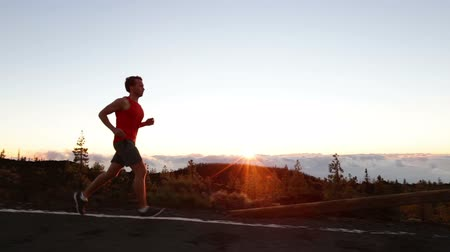 kimerül : Sport running man - male runner training outdoors jogging on mountain road in amazing landscape nature at sunset. Fit handsome jogger working out for marathon outside in summer.