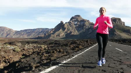 atleta : Exercising running woman athlete runner jogging on mountain road. Sport fitness girl training outside in mountains living healthy lifestyle enjoying outdoor activity. Blonde fitness model in her 20s. Stock Footage