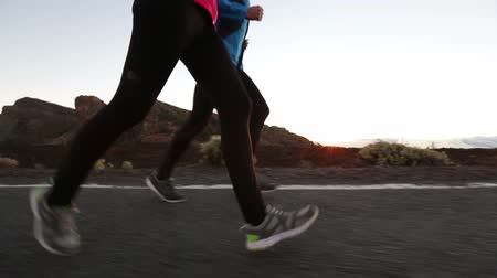 kocogó : Running - two runners jogging at mountain road at night. Running shoes to face. Athletes training together at sunset wearing tights and running jackets. Healthy lifestyle concept. Stock mozgókép