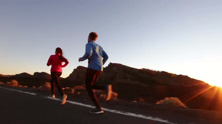 estilo de vida saudável : Healthy lifestyle people running exercising. Runners jogging on mountain road training for marathon. Asian woman and Caucasian man.