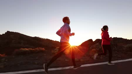 Running sport athletes woman and man jogging at night sunset. Runners training exercising on road in beautiful mountain landscape. Healthy lifestyle concept. Стоковые видеозаписи