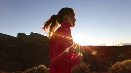 сумерки : Asian woman runner running on mountain road at sunset. Female athlete training and working out for marathon living healthy active lifestyle outdoors in beautiful nature.