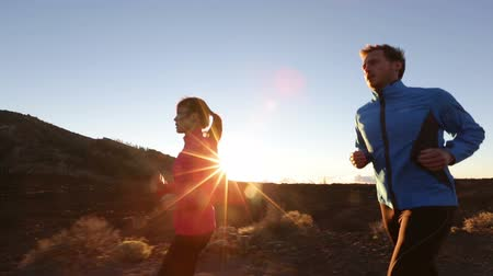 exercícios : Sport runners running exercising outdoors on road at sunset. Runner woman and man jogging training in beautiful nature landscape. Fit fitness models working out.
