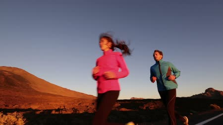 fit : Couple running jogging on road at sunset. Runner woman and man exercising and training in beautiful nature landscape.