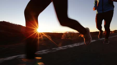 fit : Running - runner feet and shoes in action. Close up of running shoes and legs of man runner and woman runner jogging exercising at sunset on road.