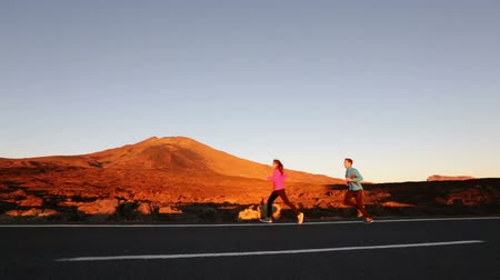 kimerül : Runners couple running at mountain road at sunset. Exercising woman and man jogging training living healthy lifestyle. Stock mozgókép