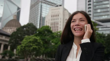 smíšené rasy osoba : Business people - woman on smart phone, Hong Kong. Asian business woman office worker talking on smartphone smiling happy. Young multiracial Chinese Asian  Caucasian female professional in Hong Kong. Dostupné videozáznamy