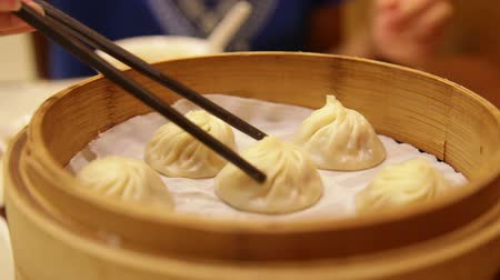bamboo steamer : Xiao long bao  xiaolongbao soup dumplings. Woman eating Chinese Shanghainese steamed dumpling buns with chopsticks in restaurant in China.
