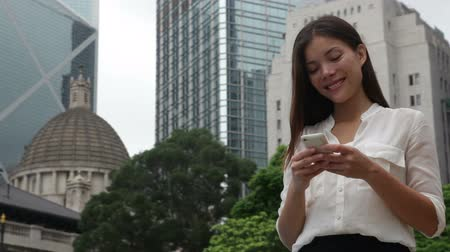 telefones : Business woman on smart phone using app and talking in Hong Kong. Asian businesswoman office worker using smartphone smiling happy. Young multiracial Chinese Asian  Caucasian female professional.