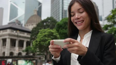 dospělý : Asian business woman using smartphone app texting sms in Hong Kong. Business woman office worker on smartphone smiling happy. Young multiracial Chinese Asian  Caucasian female professional. Dostupné videozáznamy