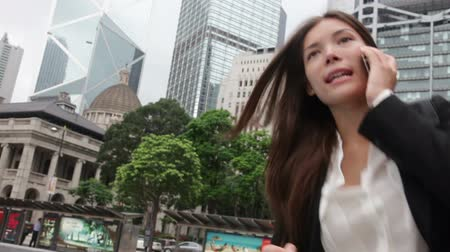 Stress - business woman running talking on smartphone stressed and rushing in a hurry. Mixed race Asian  Caucasian businesswoman stressing and busy. Video from Hong Kong Central.