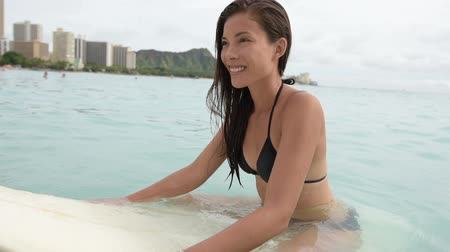 prancha de surfe : Surfing surfer girl paddle for surf on surfboard. Female bikini woman living healthy active water sports lifestyle on Hawaiian beach. Asian Caucasian model on Waikiki Beach, Oahu, Hawaii.