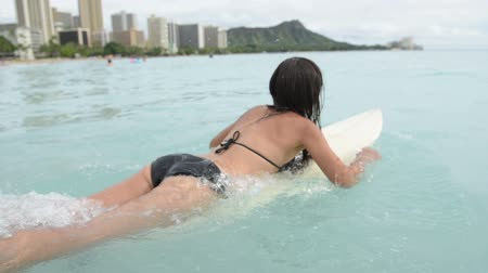детеныш : Surfing surfer girl paddle for surf on surfboard. Female bikini woman living healthy active water sports lifestyle on Hawaiian beach. Asian Caucasian model on Waikiki Beach, Oahu, Hawaii.