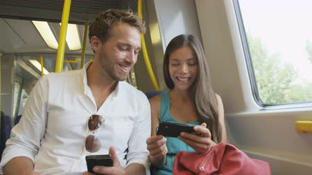 общественный : Smart phone people sharing and watching funny video laughing traveling in train on commute. Passengers using smartphone commuting in public transportation. Young multiracial Asian woman  Caucasian Man Стоковые видеозаписи