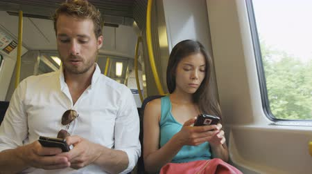 utazó : Passengers commuting using smartphones 4g wireless internet network sms texting or working while commuting to work in train. Multiracial Asian woman and Caucasian man on smart phone on commute to work