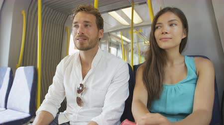 kaukázusi : Train passengers. Commuters sitting in transport smiling happy in public transportation system commuting to work or other travel. Couple  multiracial Asian woman and young Caucasian man.