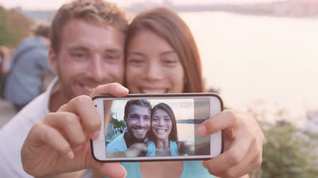 társkereső : Smart phone selfie - couple taking self portrait using smartphone camera. Dating couple in love having fun taking candid fresh picture photo laughing smiling. Caucasian man  Asian woman at sunset.