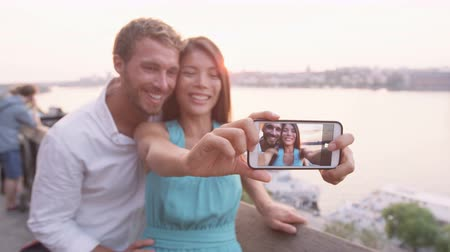 sunset city : People having fun - couple smart phone selfie self portrait in Stockholm. Dating lovers with smartphone taking candid fresh selfportrait picture photo laughing smiling. Multiracial man and woman.