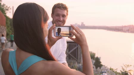 İskandinavya : Woman taking picture of boyfriend with smart phone. Couple in love dating having fun using smartphone taking photos. Tourists visiting Stockholm  Sweden. Multiracial couple  Asian woman  Caucasian man