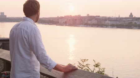 İskandinavya : Man looking at sunset enjoying view. Young man relaxing enjoying calm serene moment in solitude in Stockholm  Sweden.