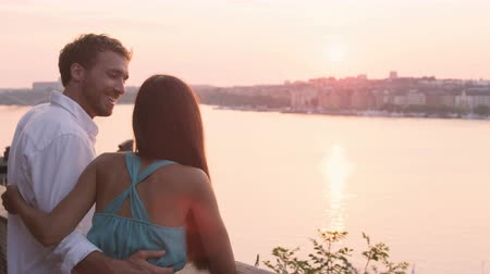 İskandinavya : Man and woman looking at view embracing at sunset. Romantic couple in love enjoying beautiful view of Stockholm  Sweden. Lovers on honeymoon in Scandinavia relaxing. Stok Video