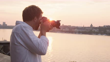 Tourist taking photograph of sunset in Stockholm skyline and Gamla Stan. Man photographer taking photos using SLR camera. Male traveler sightseeing visiting landmarks in Sweden  Scandinavia.