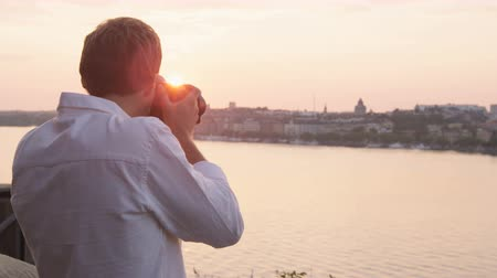Скандинавия : Photographer taking pictures of sunset in Stockholm skyline and Gamla Stan. Man tourist taking photos using SLR camera. Male traveler sightseeing visiting landmarks in Sweden  Scandinavia Стоковые видеозаписи