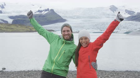 поход : Cheering happy people celebrating on Iceland hike. Cheerful elated hikers couple hiking by glacier and glacial lagoon  lake Jokulsarlon by Vatnajokull National Park in Icelandic nature.