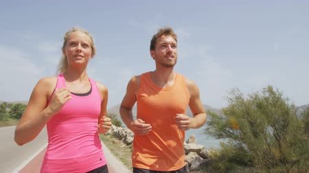 Exercising running couple jogging on beach. Runners training on sand by the ocean smiling happy in full body length. Fit fitness couple  blonde woman and Caucasian man runner. RED EPIC  SLOW MOTION.