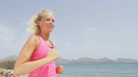 kimerül : Exercising young woman running and jogging happy on beach. Female runner athlete living healthy lifestyle outside smiling. RED EPIC, SLOW MOTION.