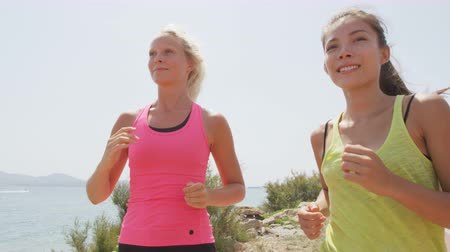 Runners - two women running outdoors training. Exercising female athletes jogging outside on beach smiling happy. Multiracial Asian and Caucasian woman in healthy lifestyle. RED EPIC  SLOW MOTION.