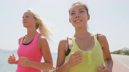 estilo de vida saudável : Healthy lifestyle women running on beach. Two girls jogging training outdoors in fitness outfit exercising together smiling happy. Multiracial asian woman and caucasian girl. RED EPIC  SLOW MOTION.