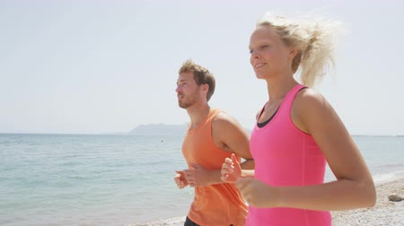 outside view : Running people. Runners couple jogging on beach training together. Man and woman joggers exercising outdoors. RED EPIC  SLOW MOTION.