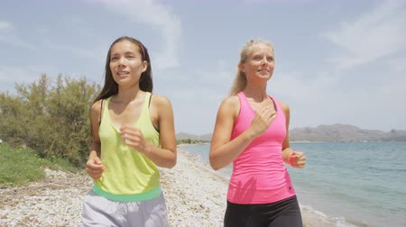 kimerül : Running women jogging on beach. Girl friends runners exercising training together for marathon run Caucasian and Asian woman running partners. RED EPIC Footage in REAL TIME. Stock mozgókép