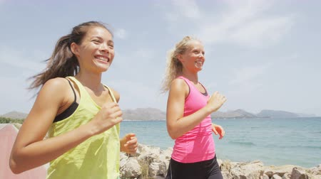 kimerül : Running women jogging on beach talking having fun laughing. Girl friends runners exercising training together for marathon run Caucasian and Asian woman running partners. RED EPIC  SLOW MOTION. Stock mozgókép