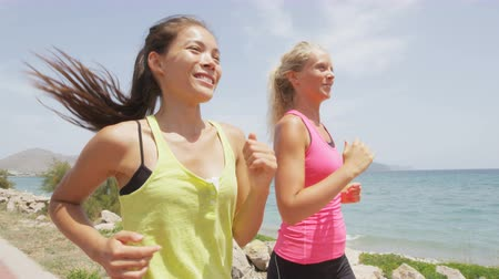 kimerül : Running women runners training outdoors. Close up portrait of happy woman runner jogging outside with friends on beach. RED EPIC footage in SLOW MOTION.