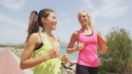 Women running exercising jogging happy on beach training as part of healthy lifestyle. Two fit female runners talking happy and smiling. Multiracial Asian and Caucasian woman. RED EPIC  SLOW MOTION.