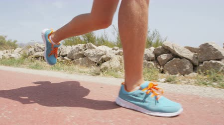 Running shoes of runner feet running on road with closeup on shoe. Man fitness athlete jogger workout in wellness concept by beach.  SLOW MOTION. Стоковые видеозаписи