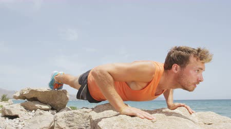 exercícios : Fitness man exercising push ups working out strength training pushups. Male fitness model cross-training on beach. Caucasian man in his twenties. RED EPIC  SLOW MOTION.