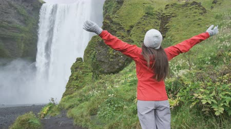 utazó : Waterfall - Happy woman by Skogafoss on Iceland serene and free outdoors. Girl visiting famous tourist attractions and landmarks in Icelandic nature landscape on the ring road. RED EPIC SLOW MOTION Stock mozgókép