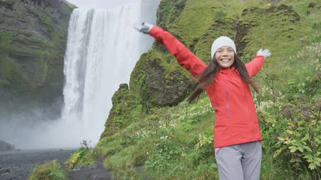 utazó : Blissful woman by waterfall Skogafoss joyful and happy turning and spinning dancing in bliss and joy on Iceland. Girl visiting tourist attraction and landmark in Icelandic nature on the ring road. Stock mozgókép