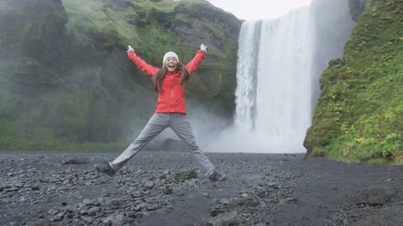 utazó : Girl jumping happy excited by waterfall on Iceland  Skogafoss  ring road. Happy woman looking at camera cheerful and joyful visiting tourist attraction landmarks in Icelandic nature. RED EPIC.