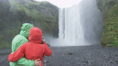 arka görünüm : Iceland tourists people fun by waterfall Skogafoss. Couple visiting famous tourist attractions and landmarks in Icelandic nature landscape on the ring road. RED EPIC SLOW MOTION.