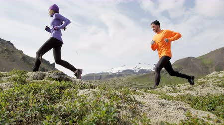 kimerül : Cross country runners in trail running sport. People  woman and man runners training jogging outdoors in beautiful mountain nature landscape on Snaefellsnes  Iceland. RED EPIC SLOW MOTION at 90 FPS. Stock mozgókép