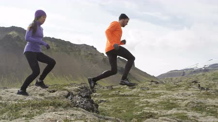 kimerül : Sport running. Runners on cross country trail jumping outdoors working out. Fit young fitness model man and asian woman training outside in mountain nature on Snaefellsnes  Iceland. RED EPIC  120 FPS.