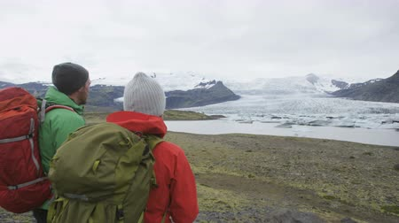 aktywność : Hiking people people trekking on glacier hike on Iceland walking by glacial lagoon  lake of Fjallsarlon  Vatna glacier  Vatnajokull National Park. Couple in Icelandic nature. RED EPIC  60 FPS Wideo