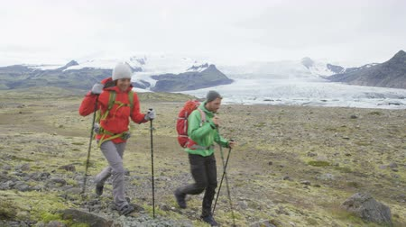 aventura : Hiking adventure travel people walking towards camera on Iceland living active healthy lifestyle wearing backpacks by glacier and glacial lagoon  lake of Fjallsarlon  Vatnajokull. RED EPIC  REAL TIME