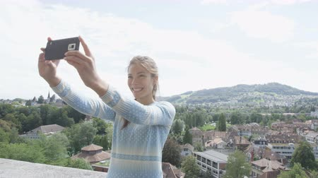 podróżnik : Selfie girl - Asian woman taking self portrait photography picture with smartphone at view point in Bern  Switzerland. Smart phone and travel concept with multicultural mixed race Asian Caucasian girl Wideo