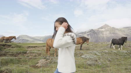 koňmo : Iceland travel concept - Icelandic horses and girl. Woman in sweater running joyful and cheerful going horseback riding smiling in beautiful nature on Iceland. RED EPIC 90 FPS.
