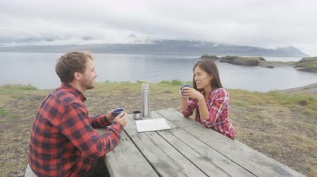 pléd : Couple camping sitting at table drinking coffee from thermos bottle flask by lake on Iceland. Campers woman and man relaxing taking break on road trip in beautiful Icelandic nature. Stock mozgókép